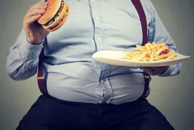 Полный мужчина гамбургером в руках