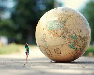 Девушка смотрит на большой глобус