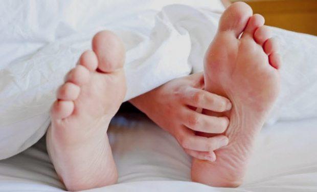 Стопы и рука торчат из-под одеяла