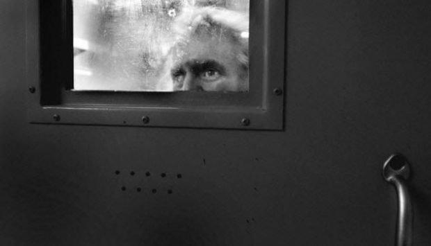 Мужчина смотрит в окно в двери