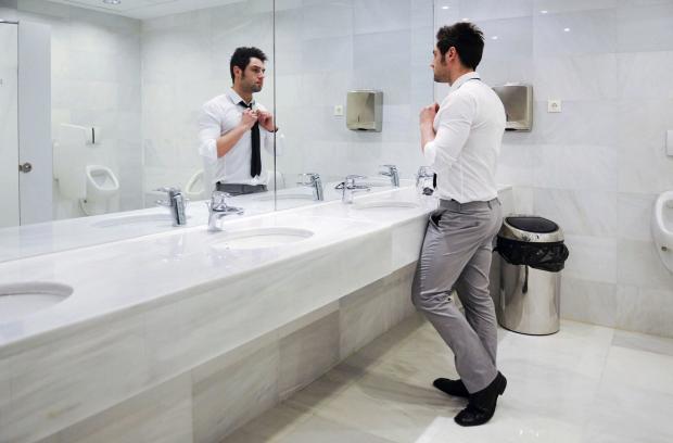 Мужчина смотрится в зеркало