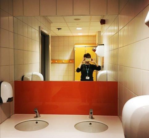 Сотрудник фирмы в фотографирует себя в зеркало