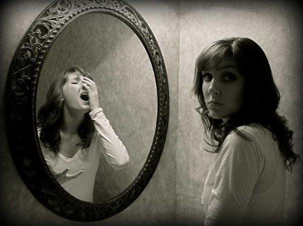 Девушка напротив зеркальной поверхности