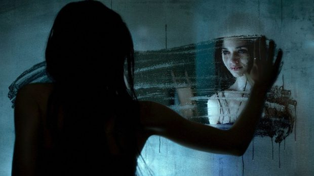 Девушка протирает запотевшее зеркало