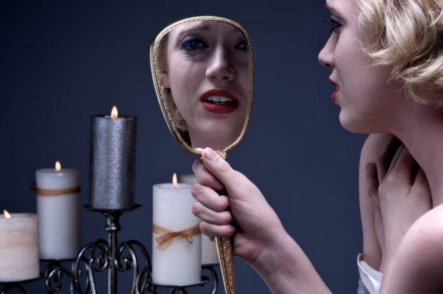 Плачущая девушка смотрит в зеркало