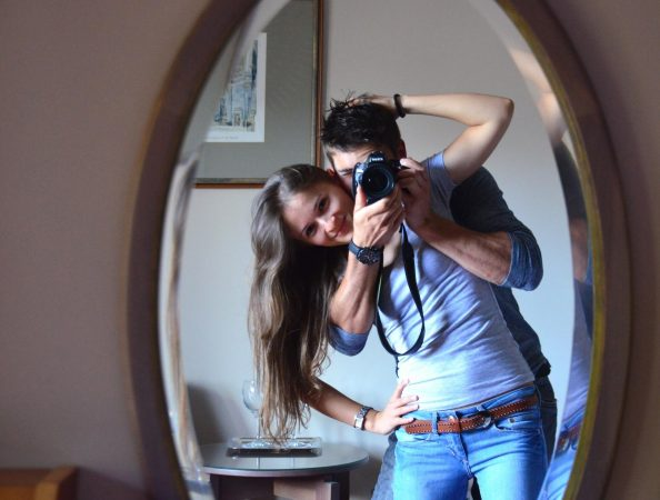 Пара фотографируется в зеркале
