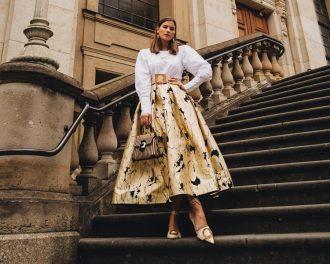 девушка стоит на ступеньках в юбке миди