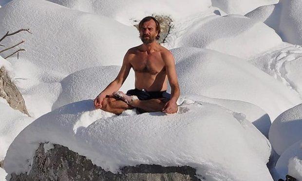 Мужчина в шортах сидит на снегу