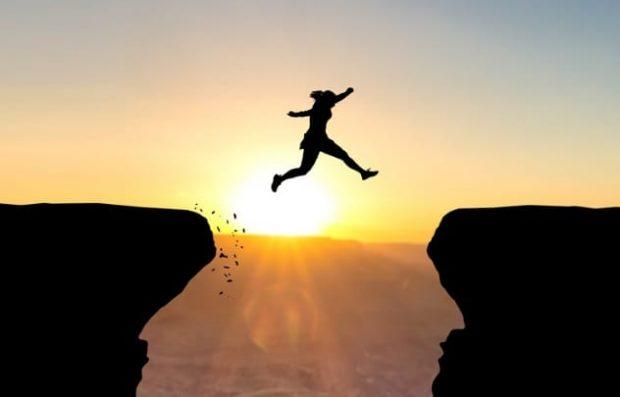 Человек прыгает над ущельем