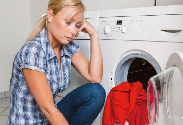 грустная женщина у стиральной машины