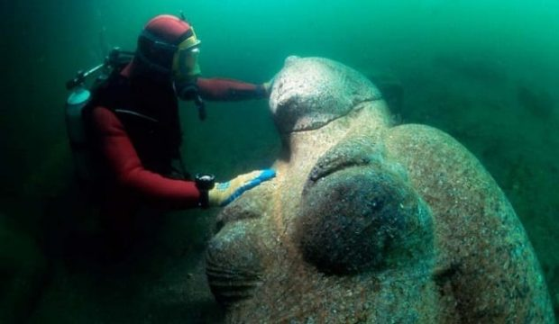 Дайвер держится за статую