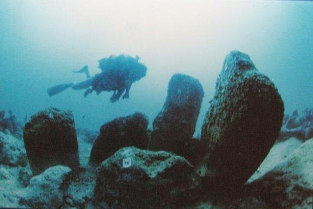 Дайвер плывёт среди руин