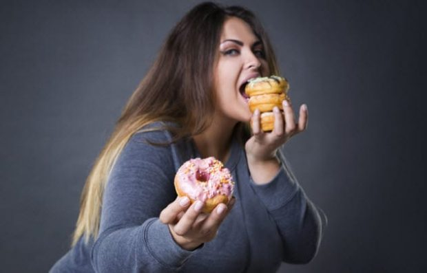 Девушка ест пончики